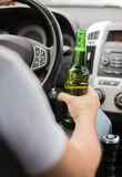 Man drinking alcohol while driving the car Stock Images