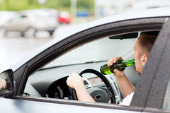 Man drinking alcohol while driving the car. Transportation and vehicle concept - man drinking alcohol while driving the car Stock Photography