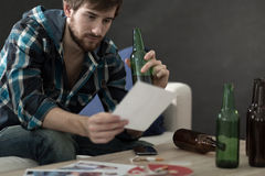 Man drinking alcohol and looking at photos Royalty Free Stock Image