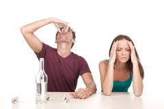 Man drinking alcohol and woman sitting upset at table. Photo of women with alcoholic husband on white background stock image