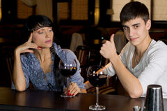 Man drinking at a bar giving a thumbs up. Handsome young men drinking a glass of red wine at a bar with a female friend giving a thumbs up of approval to show royalty free stock photos