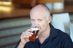 Man drinking beer. Middle aged man drinking beer from a glass in a pub, a bar or a restaurant Royalty Free Stock Images