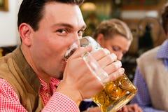 Man drinking beer in Bavarian pub. Inn or pub in Bavaria - men in traditional Tracht drinking beer Stock Photography