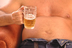 Man drinking beer with beer belly  Stock Images