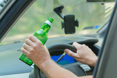 Man drinking beer in a car Stock Images