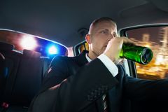 Man drinking beer chased by police. Portrait Of A Young Man Drinking Beer Chased By Police Royalty Free Stock Photography