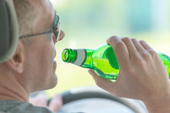 Man drinking beer while driving a car Royalty Free Stock Image