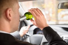 Man drinking beer while driving Stock Photography