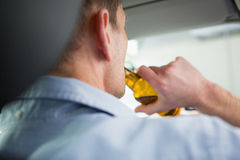 Man drinking beer while driving Stock Images