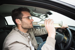 Man drinking beer while driving Stock Image