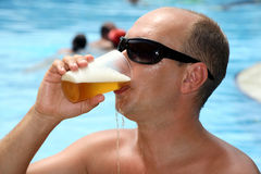 Man drinking beer and it flows in the face Royalty Free Stock Images