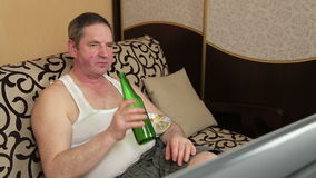 Man drinking beer at home and snack potato chip stock footage
