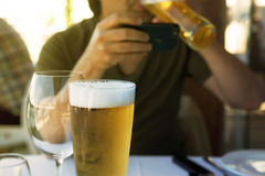 Man drinking beer and reading mobile Royalty Free Stock Images