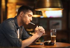 Man drinking beer and smoking cigarette at bar Stock Photos