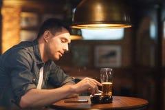 Man drinking beer and smoking cigarette at bar Stock Photos