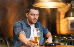 Man drinking beer and smoking cigarette at bar. People and bad habits concept - young man drinking beer and smoking cigarette at bar or pub Royalty Free Stock Images