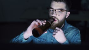 Man drinking beer and using PC