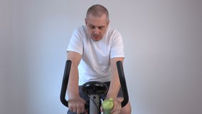 Man drinking from a bottle and used exercise bike stock video