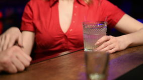 Man drinking a cocktail belonging to the girl. stock footage