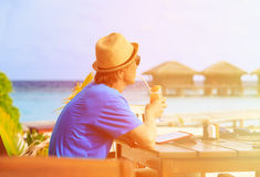 Man drinking cocktail looking at touch pad in Royalty Free Stock Photo