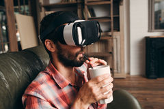 Man drinking cocktail while using vr glasses Stock Photos