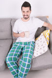 Man drinking coffee. Attractive young man drinking coffee and relaxed on couch. Indoors Royalty Free Stock Photos