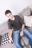 Man drinking coffee. Attractive young man drinking coffee and relaxed on couch. Indoors Stock Photo