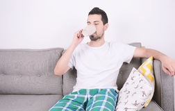 Man drinking coffee. Attractive young man drinking coffee and relaxed on couch. Indoors Stock Images