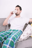 Man drinking coffee. Attractive young man drinking coffee and relaxed on couch. Indoors Stock Image