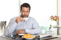 Man drinking coffee in cafe with croissant and newspaper on tabl Royalty Free Stock Images