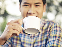Man drinking coffee. Close-up of a man drinking coffee, focus on the cup Royalty Free Stock Photo