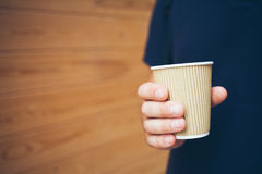 Man is drinking coffee. Close up of hands with cup of coffee, wooden background. Early morning routine Stock Images