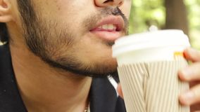 Man drinking coffee from cup. In the park stock video