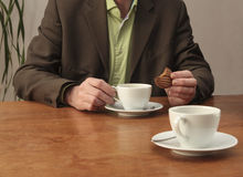 Man drinking coffee and eating cookie at desk Royalty Free Stock Photos