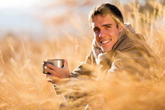Man drinking coffee fall. Cheerful young man drinking coffee outdoors in fall Royalty Free Stock Images