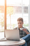 Man drinking coffee with laptop on wooden table Stock Photos