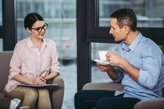 Man listening to doctor recommendations. Man drinking coffee and listening to female doctor recommendations stock images