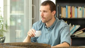 Man drinking coffee and looking away. Serious man drinking coffee and looking away in a restaurant stock video