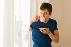 Man drinking coffee looking out the window Stock Photos