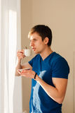 Man drinking coffee looking out the window Royalty Free Stock Photography