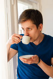 Man drinking coffee looking out the window Stock Photography