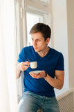 Man drinking coffee looking out the window Royalty Free Stock Image