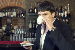 Man drinking coffee. Near the bar royalty free stock photography