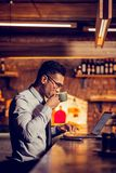 Man drinking coffee near bar counter and working remotely. Drinking coffee. Dark-haired businessman drinking coffee near bar counter and working remotely stock image
