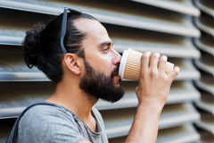 Man drinking coffee from paper cup on street Stock Images