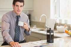 Man drinking coffee while reading newspaper Stock Photos