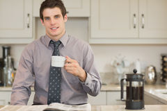 Man drinking coffee while reading newspaper Royalty Free Stock Images