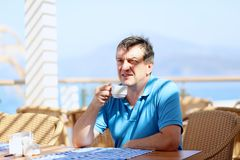 Man drinking coffee in resort restaurant Royalty Free Stock Images