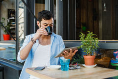 Man drinking coffee in sidewalk cafe and using digita tabl Royalty Free Stock Images