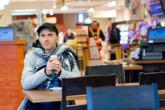 Man drinking coffee sitting in Cafe. Focus is on face. Stock Photos